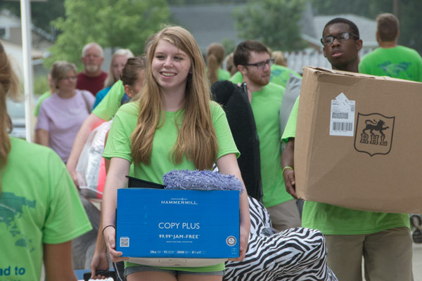 Faculty, staff and student volunteers help freshmen move in to the residence halls.