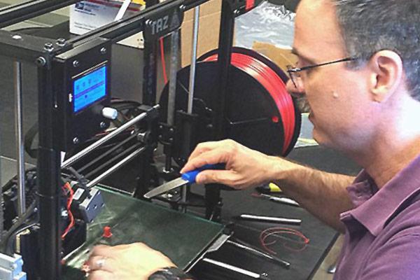 Associate professor Tim Duman removes a test object from the 3-D printer.