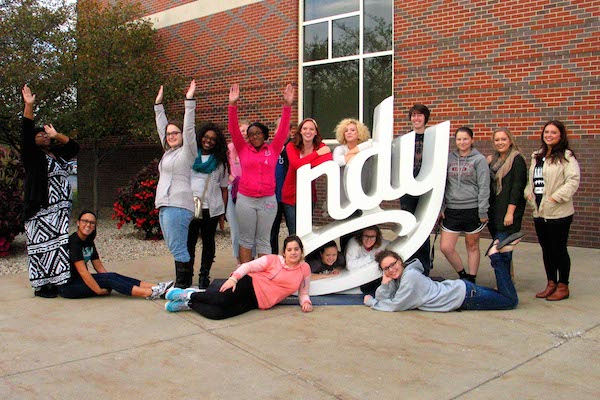 UIndy social work students pose with the 'NDY' sculpture on campus.